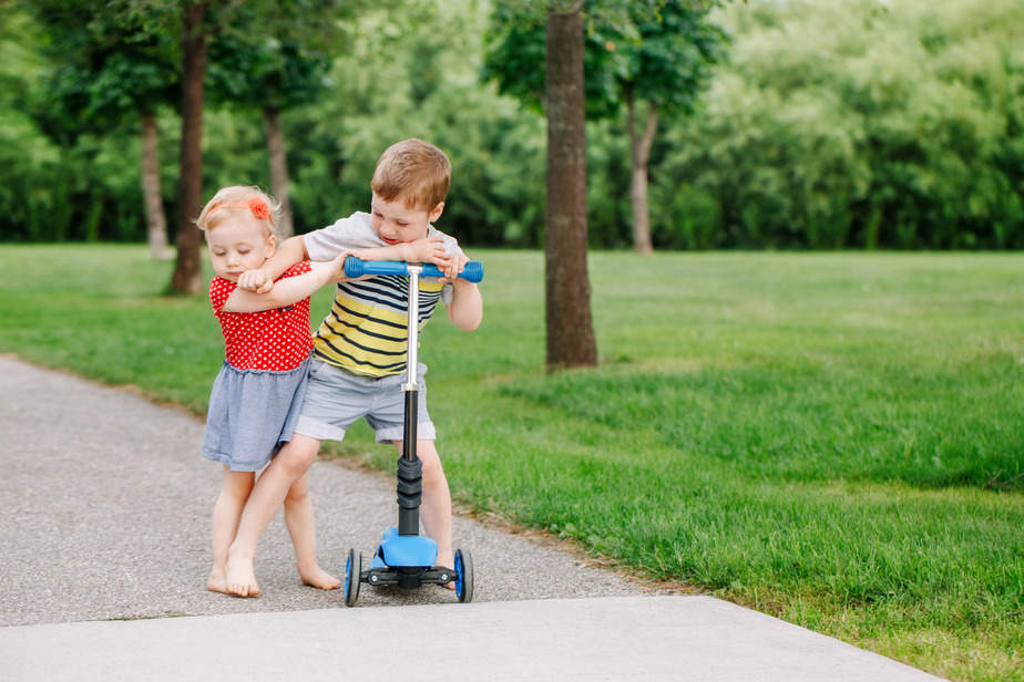 Canva – Two little Caucasian preschool children fighting hitting each other. Boy and girl can not share one scooter. Older sibling brother not giving his toy to younger sister. Communication problems.