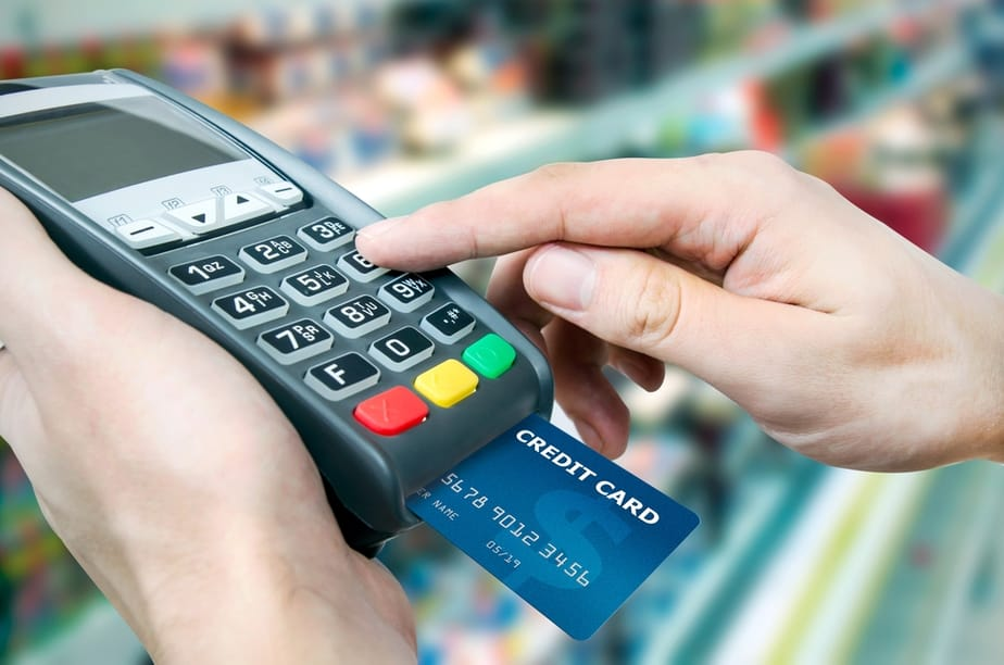 Hand with credit card swipe through terminal for sale in supermarket