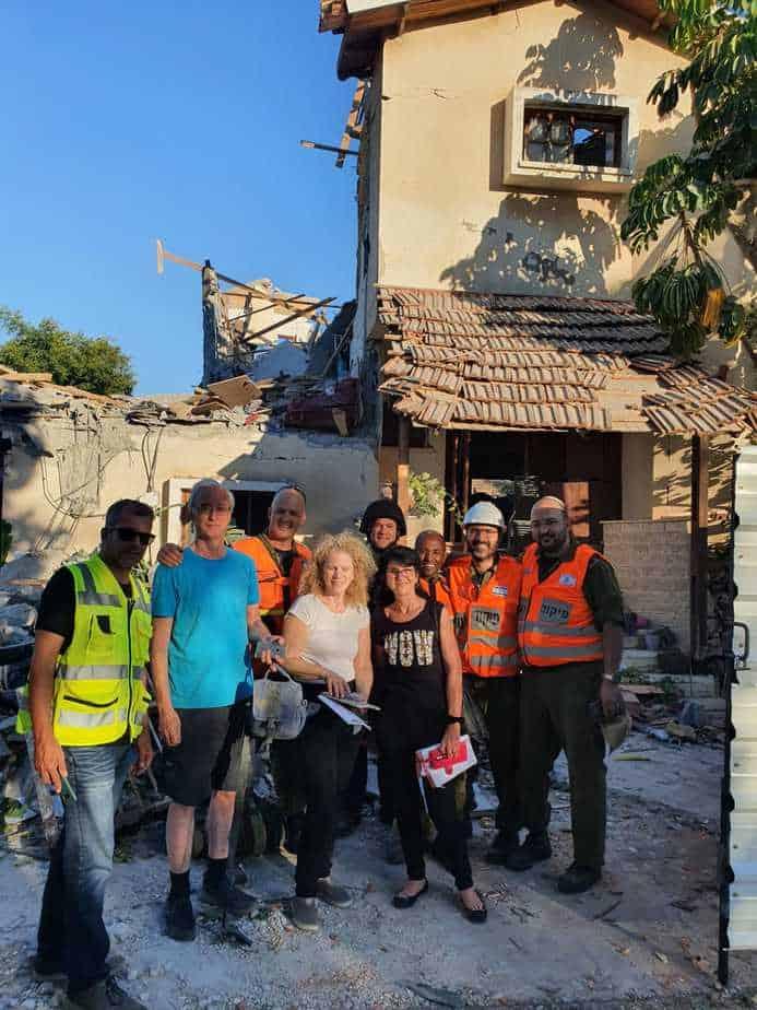 דרורה נבון עם אנשי פיקוד העורף ועיריית יהוד מונוסון על רקע ביתה. צילום: בירן גריידי