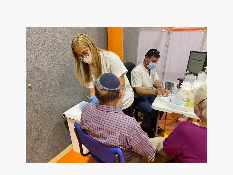 """מגי כהן מחסנת תושבים במתחם החיסונים של הכללית באור יהודה. צילום: דוברות מחוז דן-פ""""ת, כללית"""