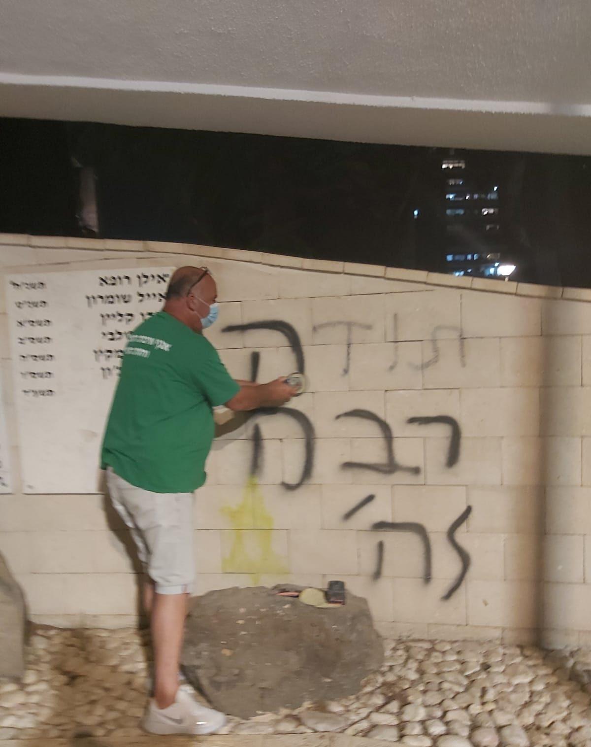 עובד עיריית יהוד-מונוסון מנקה את כתובת הגרפיטי שרוססה על האנדרטה לזכר חללי יהוד. צילום: דוברות עיריית יהוד-מונוסון